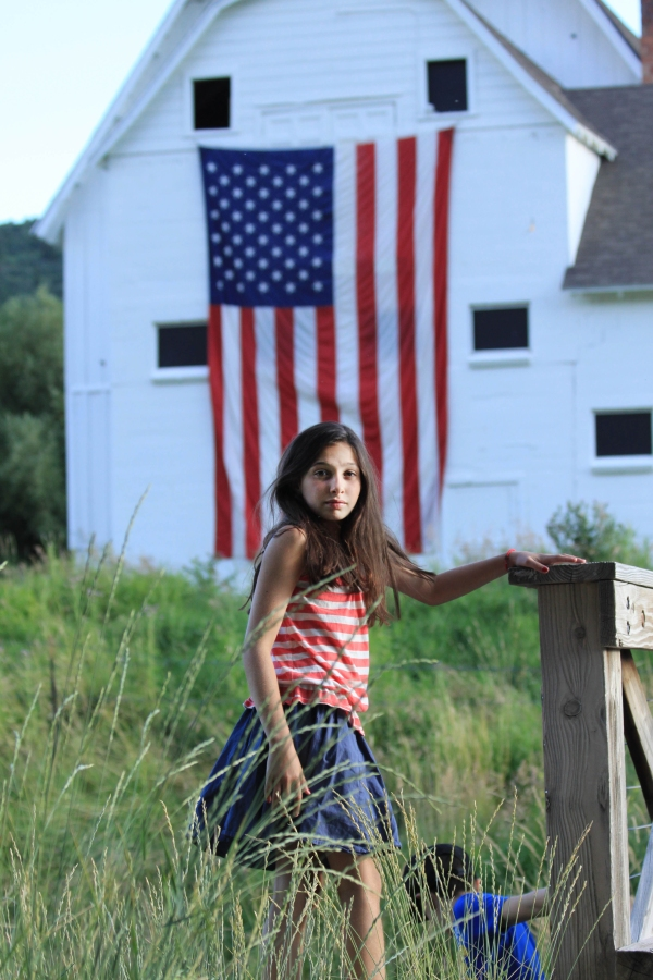 girl standing by flag