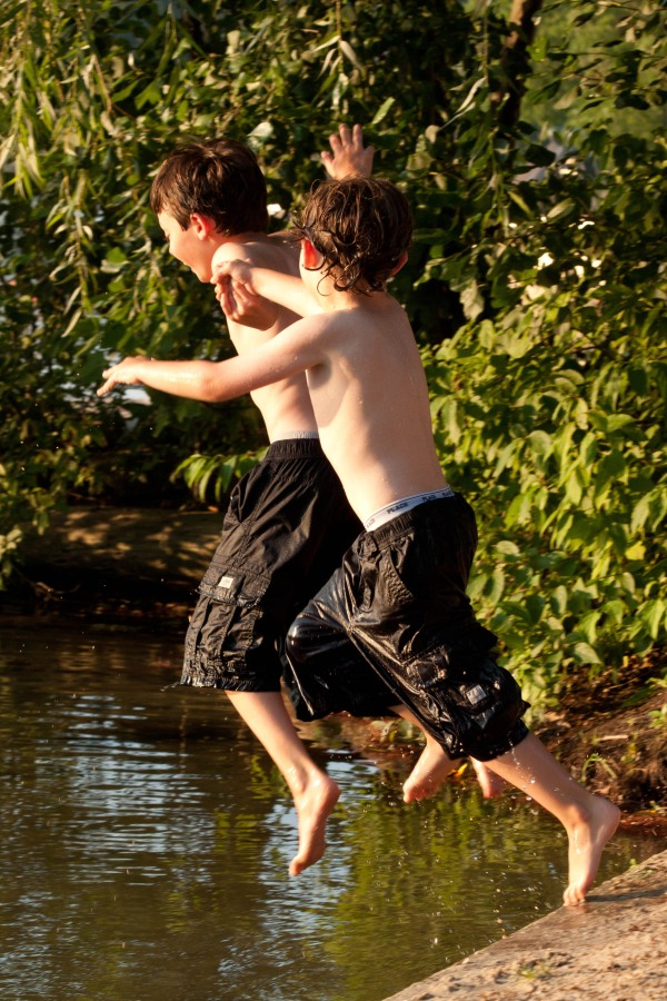 boys holding hands jumping in lake