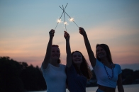 Girls playing with sparklers at sunset