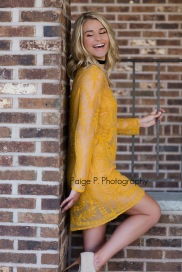 High School girl leaning against brick wall for senior portrait