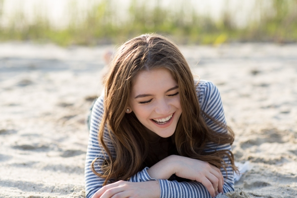 High School senior portrait, girl laughing in sand