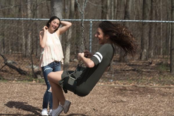 Two teen girls spinning on swingset