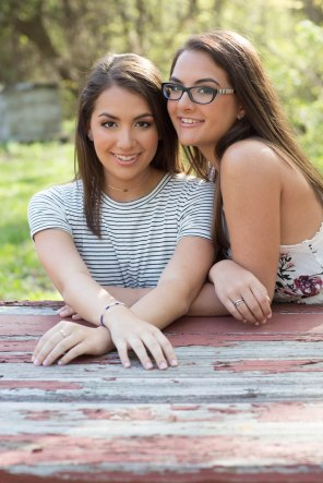 Senior High School sisters cheek to cheek for portrait