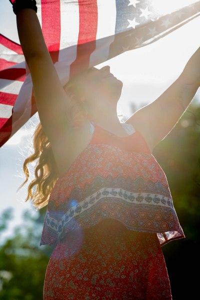 High School senior girl celebrating fourth of july under American flag