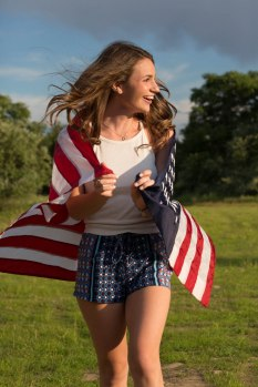 High School senior girl wrapped in American flag portrait