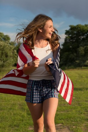 High School senior girl wrapped in American flag portrait