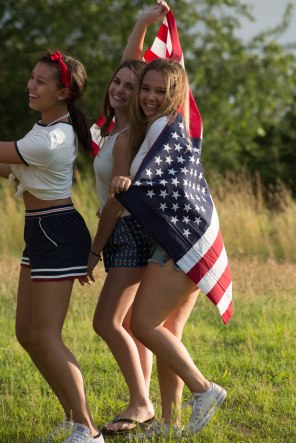High School Senior portraits carrying American flag