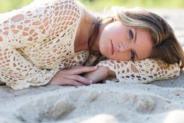 Teen portrait of a girl laying in the sand at beach